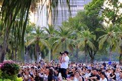 Ein Fotograf unter der Menge von Zuschauern auf dem Konzert königlichen Bangkok-Sinfonieorchesters im Lumpini-Park Stockfotografie
