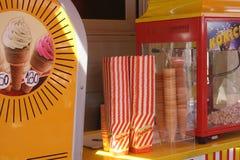 Ein fotografiertes Eiscremeplakat, eine Knall-obenmaschine für Popcorn und Plastikpopcorn bauscht sich Stockfoto