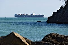 Ein Frachtschiff auf dem Horizont im gr?nen Meer lizenzfreie stockfotos