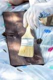 Ein Fragment einer behandschuhten Hand, die ein h?lzernes Brett mit einer breiten B?rste malt stockfotos