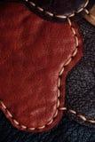 Ein Fragment einer Ledertasche und des Geldbeutels hergestellt von den mehrfarbigen Stücken Nähen des weißen Leders lizenzfreie stockbilder