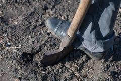 Ein Fragment eines Beines der Arbeitskraft, die mit einer Schaufel leeres b gräbt stockfotografie