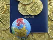 Ein Fragment eines blauen Passes und eine Kugel auf dem Hintergrund vieler Münzen der Goldfarbe lizenzfreies stockbild