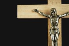 Ein Fragment eines hölzernen belichteten Kruzifixs gegen eine schwarze Rückseite lizenzfreie stockfotografie
