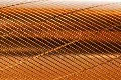Ein Fragment eines Metallobjekts mit diagonalen Kerben und einer goldenen Farbe Hintergrund und Muster stockbilder
