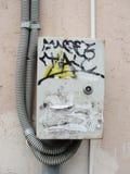 Ein Fragment von hellrosa Gipswänden mit elektrischen Kabeln und elektrischem Plattenkasten malte Graffiti stockbild
