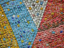 Ein Fragment von keramischen Platten eines Zusammenfassungsmosaiks auf der Wand Mehrfarbige Steine lizenzfreie stockbilder