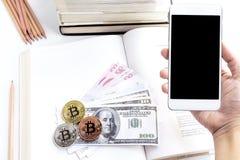 Ein Frau ` s Handgriff ein Smartphone mit Banknote und bitcoin auf Th Lizenzfreie Stockbilder