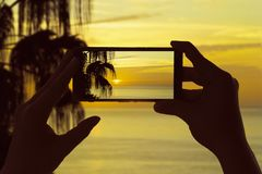 Ein Frau ` s machen Hände ein Foto des Schattenbildes der Palmen und des atlantischen Meeres auf La Gomera-Insel am Handy Kanaris Lizenzfreies Stockbild