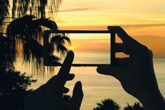 Ein Frau ` s machen Hände ein Foto des Schattenbildes der Palmen und des atlantischen Meeres auf La Gomera-Insel am Handy Kanaris Stockfotos