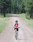 Ein Frauen-Radfahrer reitet Forest Road Lizenzfreie Stockfotos