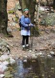 Ein Frauen-Wanderer durch Forest Creek Lizenzfreie Stockfotos