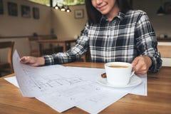 Ein Frauenarchitekt, der an Shopzeichenpapier beim Trinken des Kaffees arbeitet Lizenzfreies Stockfoto