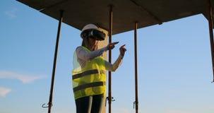 Ein Fraueningenieur an einer Baustelle in den Gläsern der virtuellen Realität bewegt ihre Hände die Arbeit der Schnittstelle simu stock video