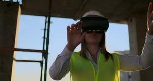 Ein Fraueningenieur an einer Baustelle in den Gläsern der virtuellen Realität bewegt ihre Hände die Arbeit der Schnittstelle simu stock footage