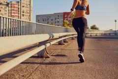 Ein Frauenläufer rüttelt auf einer Brücke in der Stadt Stockfoto