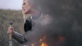 Ein Frauenritter lehnt sich an einer Klinge, die durch das Feuer sitzt und schaut herum, Zeitlupe stock footage
