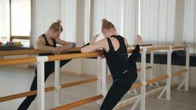 Ein Frauent?nzer oder eine Ballerinastellung an einem Ballett Barre vor dem Spiegel und tut etwas Ausdehnen Mexikanische T?nzer stock footage