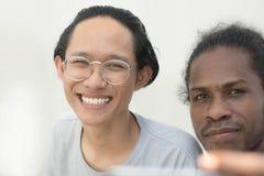 Ein Freund zwei mit unterschiedlichem ethnischem nehmendem selfie zusammen und lächelnder, asiatischer und schwarzer Mann selfie  stockfotografie