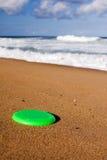 Ein Frisbee auf dem Strandsand Stockbilder