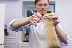Ein Friseur, der Haarschnitt für einen blonden weiblichen Kunden macht Lizenzfreie Stockfotografie