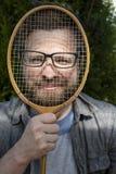 Ein froher, lustiger Mann setzte Gläser auf einen Federballschläger und lehnte sich an seinem Gesicht für einen Witz lizenzfreie stockfotos