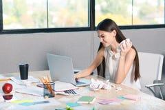 Ein frustriertes Mädchen arbeitet hinter einem Laptop und zerknitternden Papierdokumenten Innerhalb des Büros lizenzfreie stockbilder