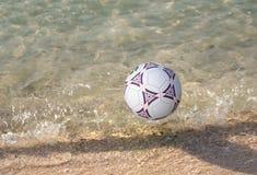 Ein Fußball, der auf Meerwasser schwimmt Stockbilder