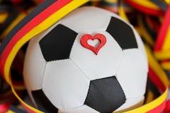 Ein Fußball, ein Herz und Ausläufer Stockbild