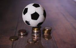 Ein Fußball oder ein Fußball und ein Stapel des Geldes Lizenzfreies Stockbild