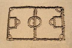 Ein Fußballnicken gezeichnet auf Sand. Stockfotos