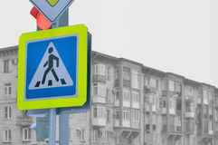 Ein Fußgängerübergangzeichen gegen ein graues Haus Stockfoto