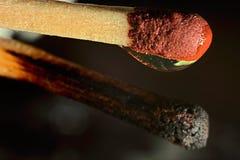 Ein ganzes Match mit einem Wassertropfen und ein gebranntes Match Makro Stockbild