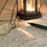 Ein geöffnetes altes Buch durch das Kerzenlicht Lizenzfreie Stockfotos