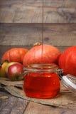 Ein geöffnetes Glasgefäß voll süße Apfelmarmelade nahe bei orange Kürbisen, ganze Äpfel auf einem hölzernen Hintergrund Autumn Ha lizenzfreies stockbild