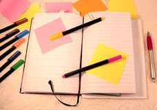 Ein geöffnetes Tagebuchbuch, klebrigen Anmerkungen und Filzstifte in varius Farben stockbild