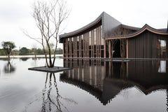 Ein Gebäude und ein Baum mit Reflexionen durch den See lizenzfreie stockfotos