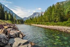 Ein Gebirgsfluss strömt unten von hohem oben im Glacier Nationalpark lizenzfreies stockfoto