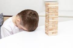 Ein gebohrter jugendlicher kaukasischer Junge, der versucht, Holzklotzturm-Brettspiel zu spielen, um sich zu unterhalten stockfoto