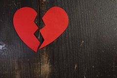 Ein gebrochenes heftiges Herz des roten Papiers auf einem rauen hölzernen Hintergrund Lizenzfreie Stockbilder