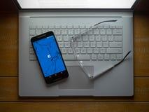 Ein gebrochenes Telefon mit dem Facebook-APP-Laden, das auf einem lapto sitzt stockbilder
