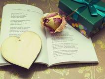 Ein Gedicht, ein hölzernes Herz, getrocknete Rosen und ein Kasten mit einem Geschenk Lizenzfreies Stockfoto