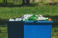 Ein gedrängter blauer Abfalleimer auf der Straße Lizenzfreies Stockfoto
