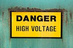 Ein Gefahrenhochspannungszeichen auf einem grünen Hintergrund Stockbild