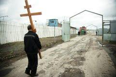 Ein Gefangener holt orthodoxes Kreuz Stockfotografie