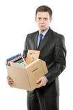 Ein gefeuerter Mann in einer Klage, die einen Kasten trägt Lizenzfreies Stockfoto