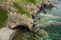 Ein geformter Felsen des Elefanten trinkt Wasser vom Meer lizenzfreie stockfotografie