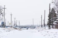 Ein gefrorener Fluss mitten in dem Dorf Lizenzfreie Stockfotos