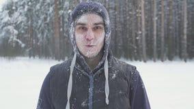 Ein gefrorener Mann entfernt seine Gläser im Winterwald, nach einem Schneesturm, bedeckt mit Schnee stock footage