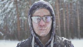 Ein gefrorener Mann mit Gläsern im Winterwald, nach einem Schneesturm, bedeckt mit Schnee stock footage